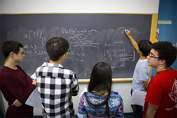 Students gathered around a blackboard